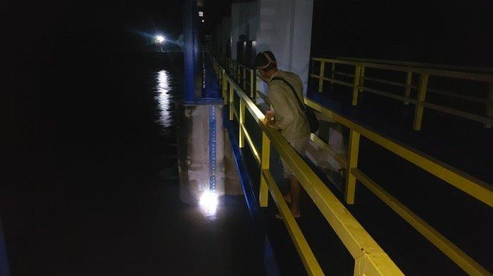 Petugas Bendung Pice saat menunjukkan tinggi air, Minggu (17/1/2021) malam. (Posbelitung.co/BryanBimantoro)