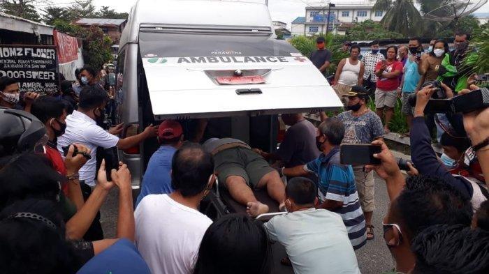 Personel kepolisian dari Polsek Siantar Selatan mengevakuasi jenazah Deny Siregar ke Ambulans RSUD Djasamen Saragih, Selasa (5/1/2021)