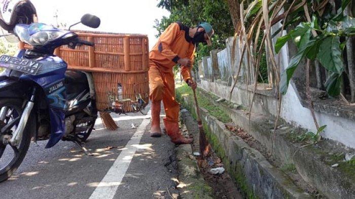 Petugas kebersihan menyapu sampah di drainase.