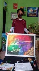 Hendrik Saputra (26) seniman kaligrafi dari Belitung, saat meperlihatkan hasil karyanya