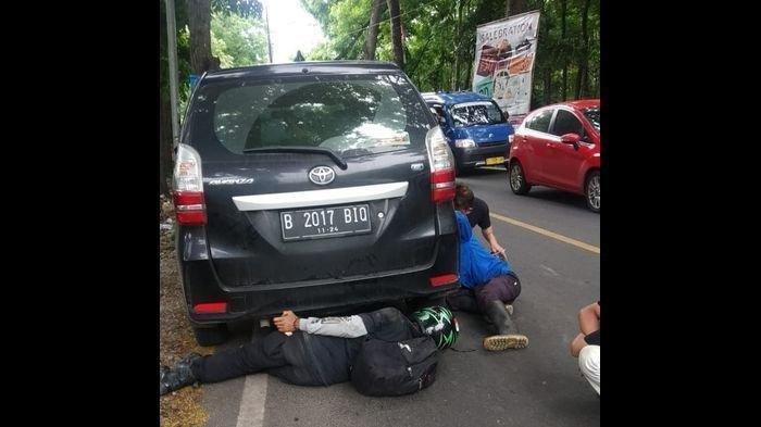 Tiga pemuda saat berusaha tarik ular sanca yang melilit ban mobil di jalan raya Jayanti, Sukabumi, Jumat (23/10/2020).
