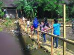 ilustrasi-masyarakat-harus-meniti-jembatan-bambu-untuk-menyeberangi-sungai.jpg