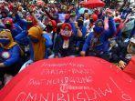 ratusan-buruh-mengenakan-payung-melakukan-unjuk-rasa.jpg