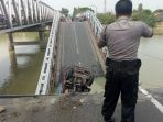 seorang-petugas-polisi-sedang-mengamankan-sekitar-jembatan-babat-lamongan-yang-ambruk_20180417_132335.jpg