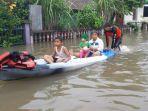 warga-menggunakan-perahu-melewati-jalan.jpg