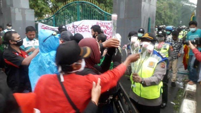Aksi pembagian bunga mewarnai unjuk rasa buruh tolak Omnibus Law UU Cipta Kerja di Cibinong, Kabupaten Bogor, Kamis (8/10/2020).