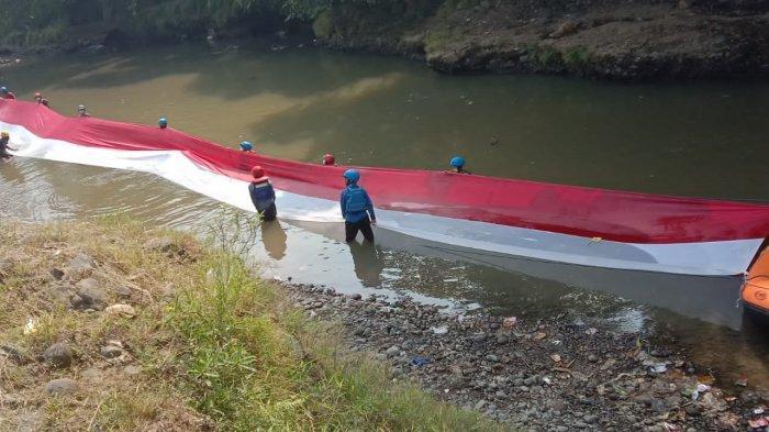 Peringati HUT ke-76 RI, Bendera Merah Putih Sepanjang 33 Meter Dibentangkan di Atas Kali Ciliwung