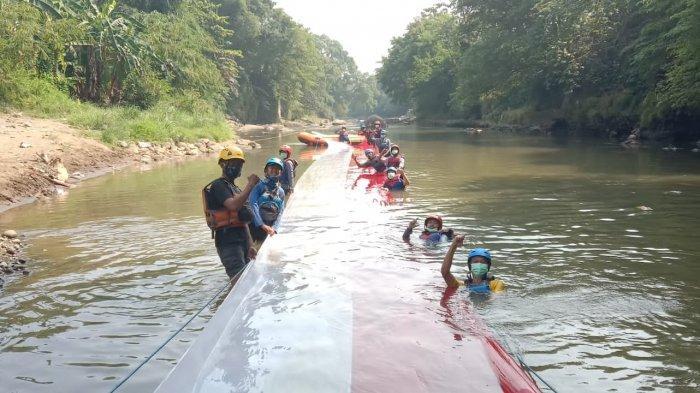 Bendera Merah Putih sepanjang 33 meter dibentangkan di atas aliran Kali Ciliwung di Kelurahan Cibuluh, Kecamatan Bogor Utara, Kota Bogor, Selasa (17/8/2021).