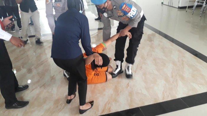 Tersangka NR (27) penjual makanan dan minuman kadaluarsa, rusak bahkan sudah tercemar menangis dan pingsan saat jumpa pers di Mako Polres Bogor, Rabu (6/10/2021).