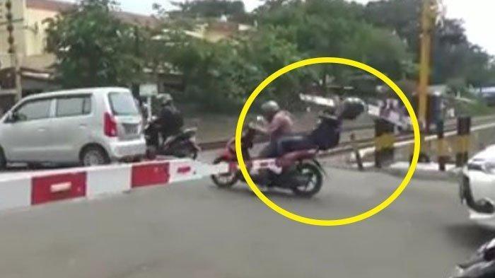 Viral Video Penumpang Sepeda Motor Terjatuh, Kepalanya Terbentur Palang Pintu Kereta