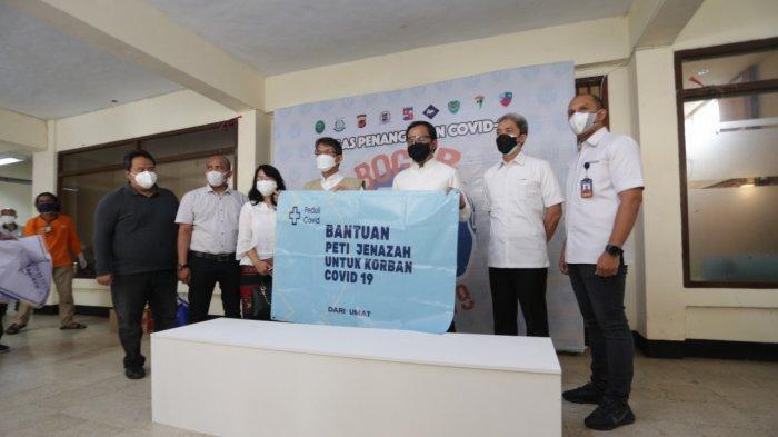 Perwakilan pengurus Yayasan Karuna Mitta Wijaya sekaligus perwakilan Grup Bluefin, Pino Siddharta menyerahkan bantuan 240 peti jenazah untuk Satgas Covid-19 Kota Bogor.