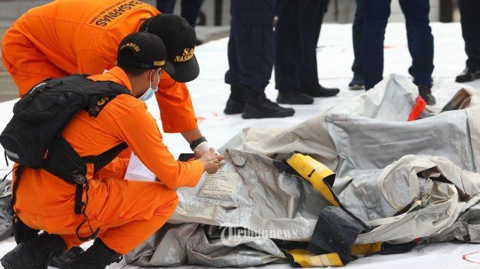 Petugas Basarnas memeriksa benda yang diduga serpihan dari pesawat Sriwijaya Air SJ 182 rute Jakarta - Pontianak yang hilang kontak di perairan Pulau Seribu, di Dermaga JICT, Jakarta, Minggu (10/1/2021). Pesawat Sriwijaya Air SJ 182 yang hilang kontak pada Sabtu (9/1) sekitar pukul 14.40 WIB di ketinggian 10 ribu kaki tersebut membawa enam awak dan 56 penumpang.