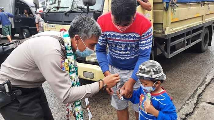 Polisi Bagikan Permen ke Warga Bojonggede yang Patuh Protokol Kesehatan