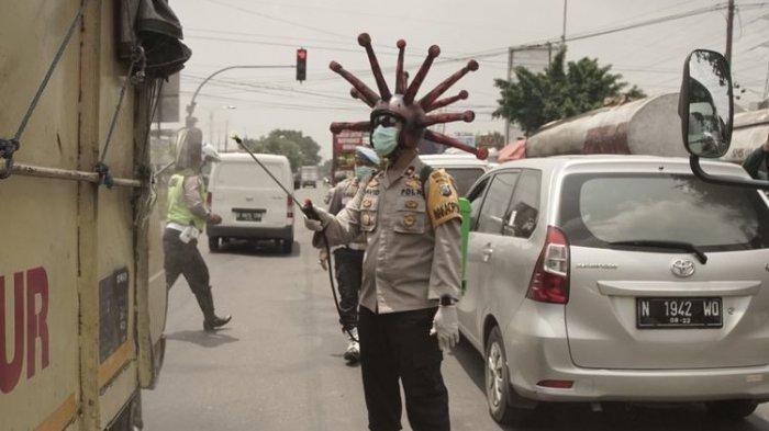Semprot Disinfektan di Jalan, Wakapolres Mojokerto Pakai Helm Virus Corona