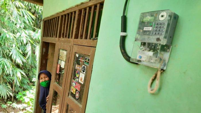 Yoyoh (50) saat menunjukan meteran listrik yang sudah terpasang di rumahnya