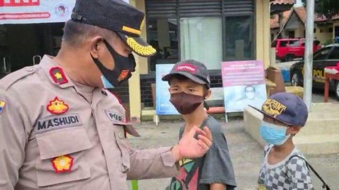 Kapolsek Losarang saat memberikan bantuan kepada dua bocah penjual kerupuk di Desa Puntang, Kecamatan Losarang, Kabupaten Indramayu, Kamis (22/7/2021).
