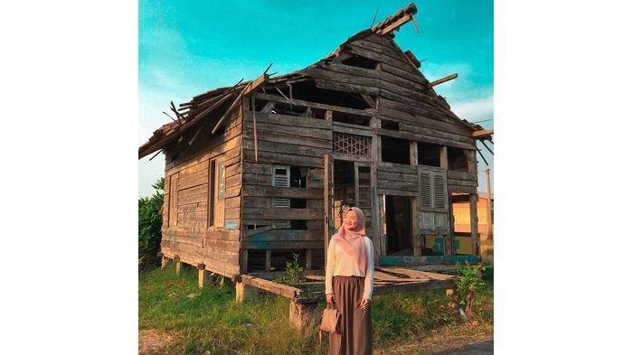 Foto seorang perempuan berlatar belakang rumah tua.