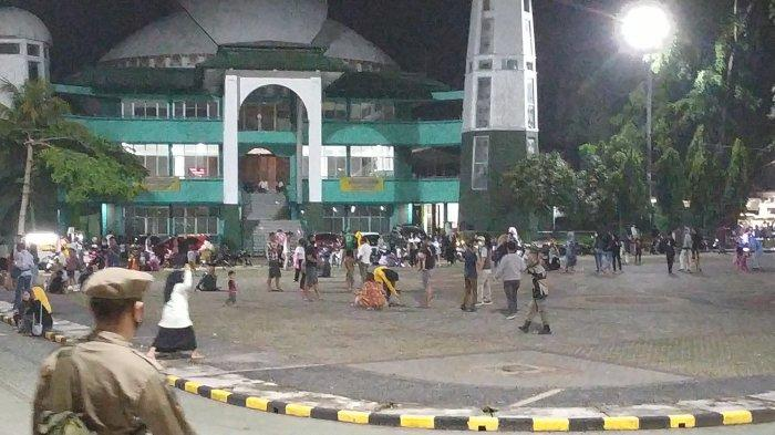 Pengunjung Alun-alun Palabuhanratu, Kabupaten Sukabumi, Jawa Barat berlarian saat dibubarkan petugas gabungan, Sabtu (27/2/2021) malam.