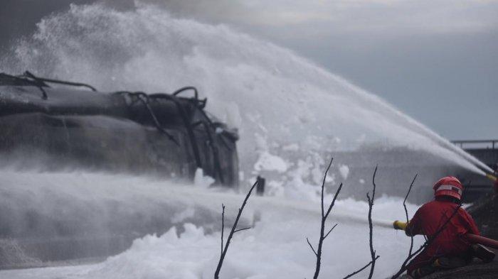 Petugas saat memadamkan api menggunakan alat Terminator Canon Foam atau meriam pelontar busa di PT Pertamina RU VI Balongan, Rabu (31/3/2021).