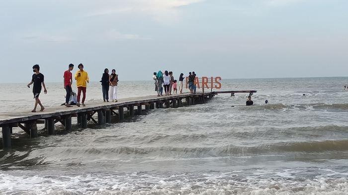 Wisatawan saat berwisata di Objek wisata Paris (Pantai Tiris) Indramayu di Desa Pabean Ilir, Kecamatan Pasekan, Kabupaten Indramayu, Minggu (29/8/2021).
