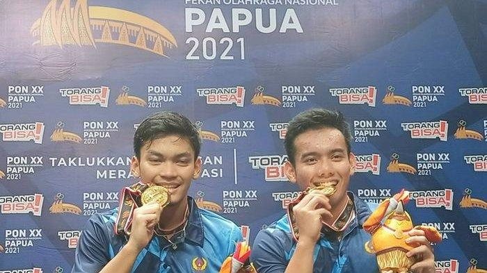 Pasangan ganda putra bulu tangkis Jawa Barat, Muhammad Shohibul Fikri dan Pramudia Kusumawardana saat merayakan kemenangan dengan memamerkan medali emas PON XX Papua 2021 -