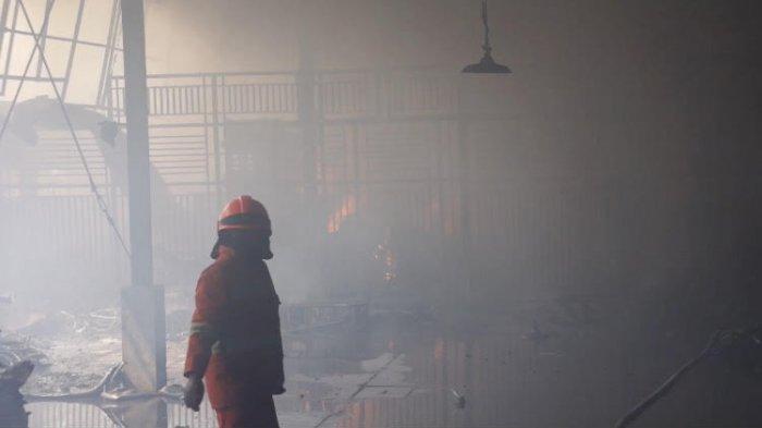 Petugas pemadam kebakaran memadamkan api yang membakar pabrik sepeda  di Jalan Babakan Ciparay, Kecamatan Bojongloa Kaler, Kota Bandung, Selasa (13/7/2021)