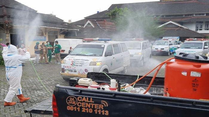 Petugas Dinas Kesehatan Kota Tasikmalaya menyemprotkan disinfektan ke mobil ambulans seusai membawa santri pasien Covid-19 di tempat isolasi Hotel Crown, Senin (15/2/2021).
