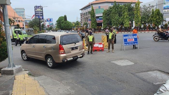 Sejumlah petugas saat memutar balik kendaraan berpelat nomor genap dalam uji coba sistem ganjil genap di simpang empat Gunungsari, Kota Cirebon, Jumat (13/8/2021).