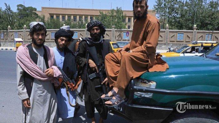 Pejuang Taliban berpose saat mereka berjaga di sepanjang pinggir jalan di Herat. Afghanistan, pada 14 Agustus 2021.