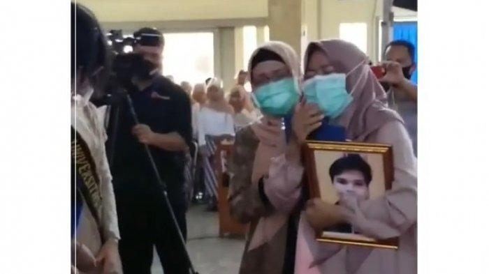 Tangkapan layar seorang ibu saat mewakili prosesi wisuda anaknya yang sudah meninggal dunia di Universitas Wiralodra Indramayu, Selasa (29/9/2020).