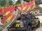 aipda-citro-di-atas-mobil-patroli-sedang-menurunkan-bambu-di-polsek-sukaresmii.jpg