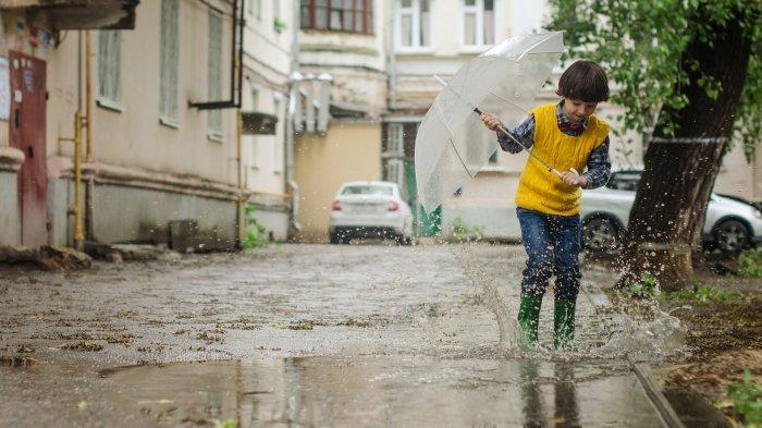 Ilustrasi anak bermain di tengah guyuran hujan