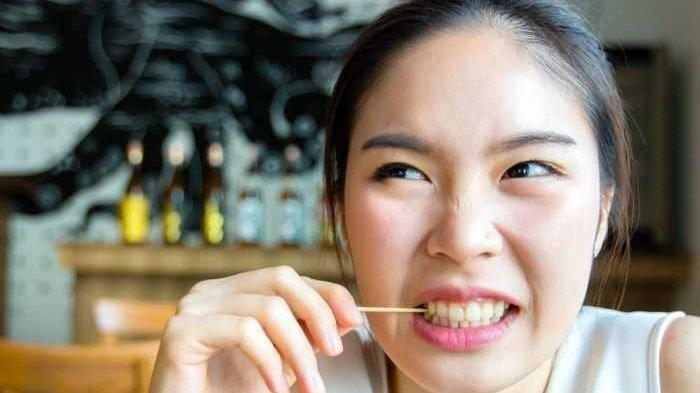 Ilustrasi membersihkan sisa makanan menggunakan tusuk gigi