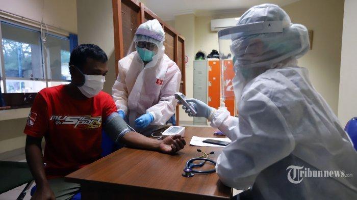 Petugas kesehatan melakukan pemeriksaan rutin pada warga yang berada di tempat penampungan sementara penanganan Covid-19 di Gelanggang Olahraga Remaja (GOR) Karet Tengsin, Jakarta Pusat, Jumat (12/6/2020).