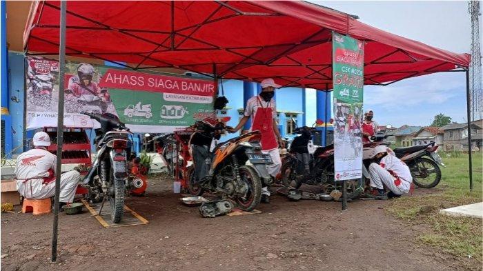 Mekanik sepeda motor Honda sedang melakukan pemeriksaan sepeda motor Honda yang terendam banjir di wilayah Indramayu (17/2)