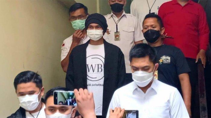 Anji eks Drive yang mengenakan kaus putih, kardigan hitam, masker, dan tutup kepala hitam ketika dibawa ke ruang pemeriksaan kesehatan. Anji terjerat kasus dugaan penyalahgunaan narkoba.