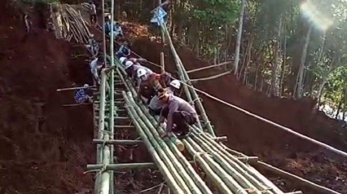 Aparat gabungan membuat jembatan darurat di lokasi longsor yang menghancurkan jembatan di Kampung/Desa Bugel, Kecamatan Ciawi, Kabupaten Tasikmalaya, Kamis (11/6/2020).