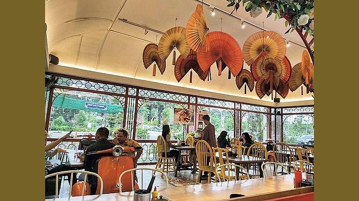 Area outdoor di Pho Ngon Paris Van Java yang dipecantik ornamen kipas bercorak warna merah dan orange.