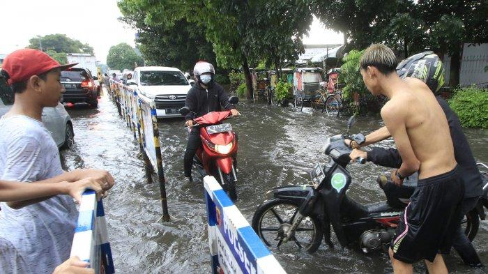 Warga membantu memutar arah pengendara motor yang terjebak banjir di Jalan Mohamad Toha, Bandung, Rabu (23/12/2020). Hujan deras yang mengguyur sebagian Kota Bandung, membuat ruas jalan tergenang banjir luapan dari saluran drainase.
