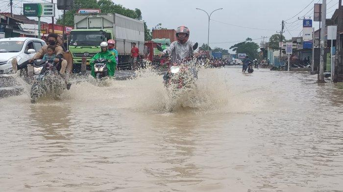 Banjir yang menggenangi Jalur Pantura di Desa Jangga, Kecamatan Losarang, Kabupaten Indramayu, Senin (8/2/2021).