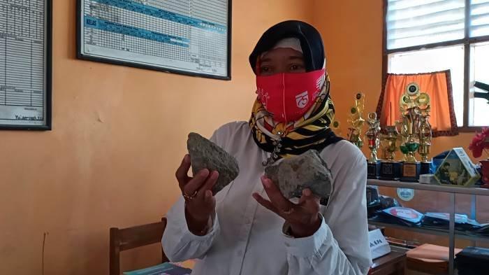 Seorang guru menunjukkan batu yang dilemparkan ke ruangan di SMP PGRI Sindang Indramayu, Rabu (13/10/2021).