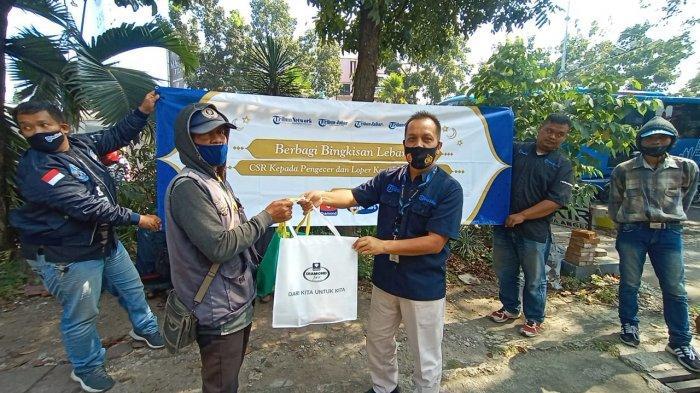 BERIKAN BINGKISAN LEBARAN - Vice GM Tribun Jabar, Purnomo, secara simbolis memberikan bingkisan lebaran kepada perwakilan pengecer koran Tribun Jabar di perempatan Jalan LLRE Martadinata-Ahmad Yani, Kota Bandung, Senin (10/5).