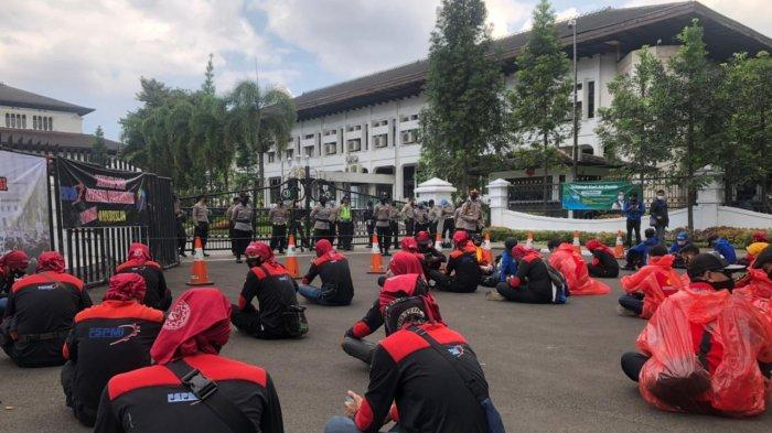 Sejumlah buruh dari KASBI menggunakan alat pelindung diri (APD) saat menggelar aksi di depan Gedung Sate, Sabtu (1/5/2021).