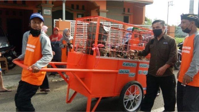 Anggota DPRD Kabupaten Ciamis dari Fraksi PKS H. Uus Rusdiana bersama warga mendorong gerobak sampah