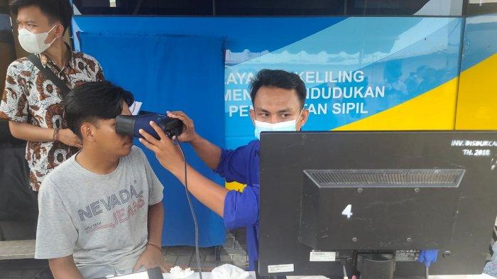 Seorang warga menikmati pelayanan administrasi kependudukan dalam program Dukcapil Ngabuburit di Islamic Center Indramayu, Kamis (15/4/2021).