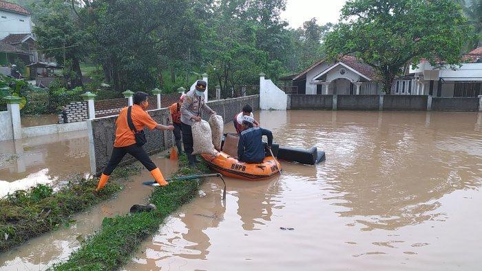 BPBD dan Polsek Mande membantu evakuasi warga yang rumahnya terendam banjir, Rabu (28/4/2021) pagi.
