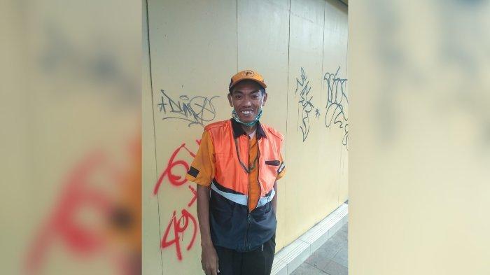 Sosok Hermawan tukang parkir yang memfoto Akbar pemulung yang viral ngaji di emperan