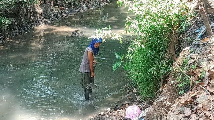 Entin Supriatin (55), warga Cipicung, Desa Karangsari, Kecamatan Padaherang, Kabupaten Pangandaran, sedang mencari pasir.