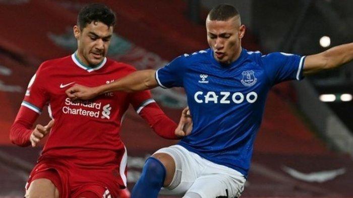Richarlison menendang bola dibayangi oleh Ozan Kabak dalam laga Liverpool vs Everton pada pekan ke-25 Premier League 2020-2021 yang dilangsungkan di Stadion Anfield, Minggu (21/2/2021) dini hari WIB.
