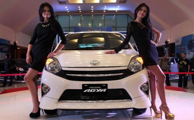 TOYOTA AGYA - Dua orang model berpose di samping mobil Astra Toyota Agya saat acara peluncuran tersebut di Graha Tirta Siliwangi, Jalan Lombok, Kota Bandung, Jumat (27/9). Mobil yang dihadirkan sebagai salah satu upaya merespon kebijakan pemerintah berupa mobil murah sekaligus melengkapi product line-up Toyota di segmen compact car dengan 1.000 cc tersebut hadir dalam tiga pilihan tipe yang dijual dari mulai harga Rp 101.400.000 hingga Rp 122.250.000 per unit.